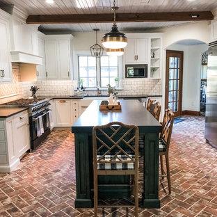 フィラデルフィアの中くらいのカントリー風おしゃれなキッチン (エプロンフロントシンク、落し込みパネル扉のキャビネット、白いキャビネット、ソープストーンカウンター、白いキッチンパネル、サブウェイタイルのキッチンパネル、シルバーの調理設備、レンガの床、赤い床、黒いキッチンカウンター) の写真