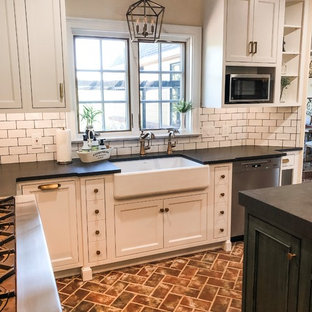 Mid-sized country u-shaped eat-in kitchen in Philadelphia with a farmhouse sink, recessed-panel cabinets, white cabinets, soapstone benchtops, white splashback, subway tile splashback, stainless steel appliances, brick floors, with island, red floor and black benchtop.