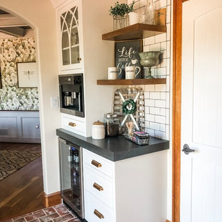 This is an example of a medium sized country u-shaped kitchen/diner in Philadelphia with a belfast sink, recessed-panel cabinets, white cabinets, soapstone worktops, white splashback, metro tiled splashback, stainless steel appliances, brick flooring, an island, red floors and black worktops.