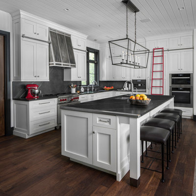 Inspiration for a coastal l-shaped dark wood floor and brown floor kitchen remodel in Detroit with an undermount sink, shaker cabinets, white cabinets, gray backsplash, stone slab backsplash, stainless steel appliances, an island and gray countertops