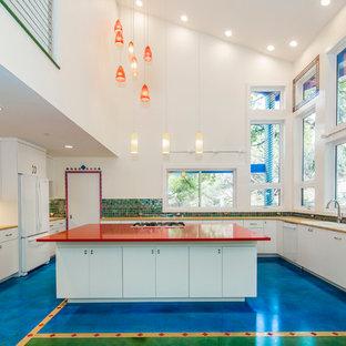 オースティンの中くらいのエクレクティックスタイルのおしゃれなキッチン (フラットパネル扉のキャビネット、白いキャビネット、マルチカラーのキッチンパネル、ガラスタイルのキッチンパネル、白い調理設備、コンクリートの床) の写真