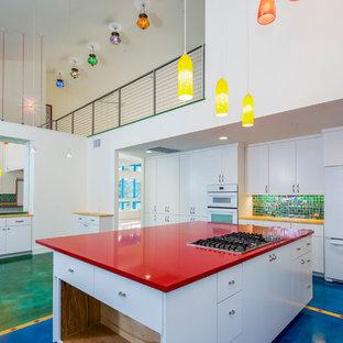 Mittelgroße Eklektische Wohnküche in U-Form mit flächenbündigen Schrankfronten, weißen Schränken, bunter Rückwand, Rückwand aus Glasfliesen, weißen Elektrogeräten, Betonboden und Kücheninsel in Austin