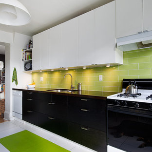 Example of a mid-sized trendy porcelain floor enclosed kitchen design in Toronto with an undermount sink, flat-panel cabinets, black cabinets, quartz countertops, green backsplash, subway tile backsplash and white appliances