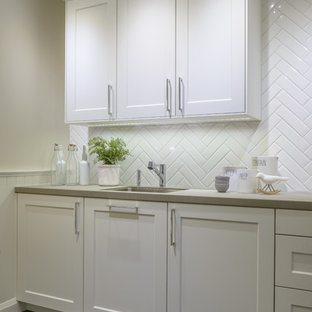Inspiration for a mid-sized transitional l-shaped eat-in kitchen in Toronto with shaker cabinets, white cabinets, quartzite benchtops, white splashback, ceramic splashback, stainless steel appliances, slate floors, no island, an undermount sink and blue floor.