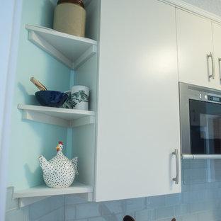 バンクーバーの小さいトランジショナルスタイルのおしゃれなキッチン (ドロップインシンク、フラットパネル扉のキャビネット、グレーのキャビネット、ラミネートカウンター、グレーのキッチンパネル、ガラスタイルのキッチンパネル、シルバーの調理設備の、セラミックタイルの床、アイランドなし) の写真