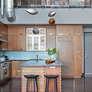トロントの中サイズのインダストリアルスタイルのおしゃれなキッチン (アンダーカウンターシンク、フラットパネル扉のキャビネット、中間色木目調キャビネット、御影石カウンター、青いキッチンパネル、ガラス板のキッチンパネル、シルバーの調理設備の、濃色無垢フローリング、茶色い床) の写真