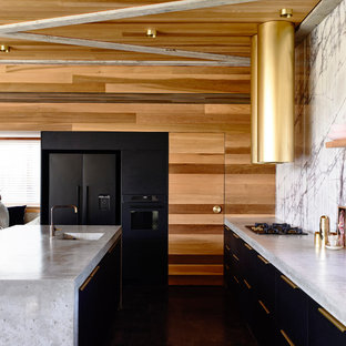 Design ideas for a contemporary galley open plan kitchen in Melbourne with an integrated sink, flat-panel cabinets, black cabinets, concrete benchtops, white splashback, black appliances, with island and grey benchtop.