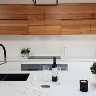 Diseño de cocina comedor lineal, contemporánea, de tamaño medio, con fregadero bajoencimera, armarios con paneles lisos, puertas de armario de madera oscura, encimera de cuarzo compacto, salpicadero blanco, salpicadero de azulejos de cerámica, electrodomésticos de acero inoxidable, suelo de terrazo, una isla y suelo blanco