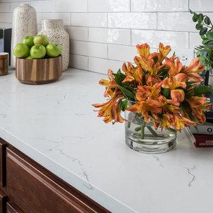 ダラスの中サイズのサンタフェスタイルのおしゃれなキッチン (アンダーカウンターシンク、シェーカースタイル扉のキャビネット、濃色木目調キャビネット、大理石カウンター、白いキッチンパネル、セラミックタイルのキッチンパネル、シルバーの調理設備の、セラミックタイルの床、ベージュの床、白いキッチンカウンター) の写真