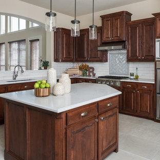 ダラスの中くらいのサンタフェスタイルのおしゃれなキッチン (アンダーカウンターシンク、シェーカースタイル扉のキャビネット、濃色木目調キャビネット、白いキッチンパネル、セラミックタイルのキッチンパネル、シルバーの調理設備、白いキッチンカウンター) の写真