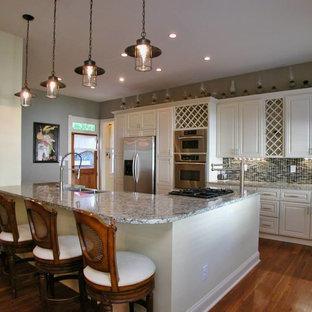 アトランタの大きいヴィクトリアン調のおしゃれなキッチン (アンダーカウンターシンク、レイズドパネル扉のキャビネット、白いキャビネット、御影石カウンター、マルチカラーのキッチンパネル、セラミックタイルのキッチンパネル、シルバーの調理設備の、無垢フローリング、茶色い床) の写真