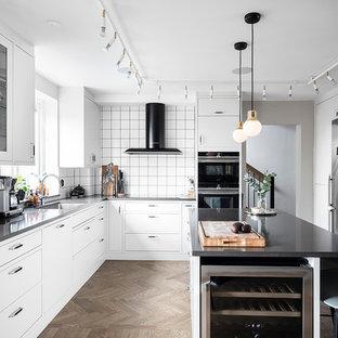 Idéer för stora skandinaviska svart kök, med vita skåp, bänkskiva i koppar, vitt stänkskydd, stänkskydd i keramik, rostfria vitvaror, en köksö, brunt golv, en undermonterad diskho och mellanmörkt trägolv
