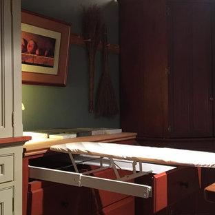 フィラデルフィアの中くらいのヴィクトリアン調のおしゃれなキッチン (エプロンフロントシンク、シェーカースタイル扉のキャビネット、濃色木目調キャビネット、木材カウンター、パネルと同色の調理設備、無垢フローリング) の写真