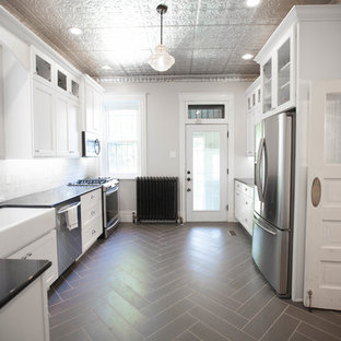 This is an example of a mid-sized traditional u-shaped separate kitchen in St Louis with a farmhouse sink, shaker cabinets, white cabinets, stone tile splashback, granite benchtops, white splashback, stainless steel appliances, vinyl floors and no island.
