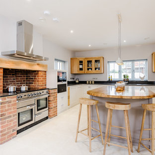 Photo of a large rural u-shaped enclosed kitchen in Essex with a submerged sink, recessed-panel cabinets, beige cabinets, granite worktops, orange splashback, brick splashback, stainless steel appliances, an island, grey floors and black worktops.