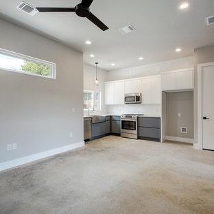 Offene, Mittelgroße Moderne Küche ohne Insel in L-Form mit Landhausspüle, flächenbündigen Schrankfronten, grauen Schränken, Küchenrückwand in Weiß, Küchengeräten aus Edelstahl, Teppichboden und buntem Boden in Austin