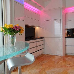 Inredning av ett modernt avskilt, stort u-kök, med en nedsänkt diskho, släta luckor, bänkskiva i glas, svart stänkskydd, glaspanel som stänkskydd, rostfria vitvaror, vita skåp, marmorgolv, en halv köksö och orange golv