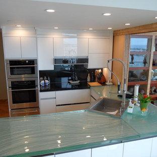 マイアミの広いモダンスタイルのおしゃれなキッチン (ドロップインシンク、フラットパネル扉のキャビネット、ガラスカウンター、黒いキッチンパネル、ガラス板のキッチンパネル、シルバーの調理設備、白いキャビネット、濃色無垢フローリング、オレンジの床、ターコイズのキッチンカウンター) の写真