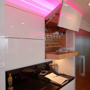 マイアミの大きいモダンスタイルのおしゃれなキッチン (ドロップインシンク、フラットパネル扉のキャビネット、ガラスカウンター、黒いキッチンパネル、ガラス板のキッチンパネル、シルバーの調理設備の、白いキャビネット、オレンジの床) の写真