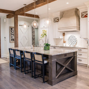 Country galley kitchen in St Louis with recessed-panel cabinets, beige cabinets, white splashback, subway tile splashback, with island, a farmhouse sink, white appliances and light hardwood floors.