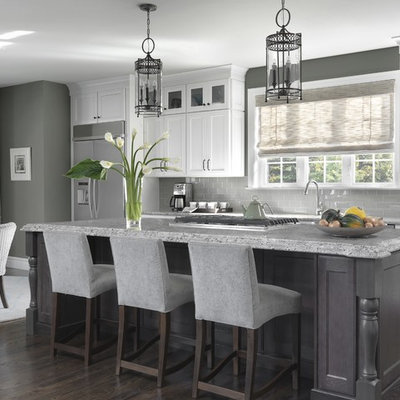 Inspiration for a timeless dark wood floor and brown floor eat-in kitchen remodel in St Louis with recessed-panel cabinets, white cabinets, gray backsplash, subway tile backsplash, stainless steel appliances, an island and gray countertops