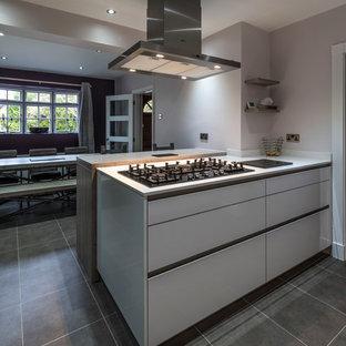 マンチェスターの中くらいのコンテンポラリースタイルのおしゃれなキッチン (一体型シンク、フラットパネル扉のキャビネット、白いキャビネット、珪岩カウンター、赤いキッチンパネル、ガラス板のキッチンパネル、黒い調理設備、クッションフロア) の写真