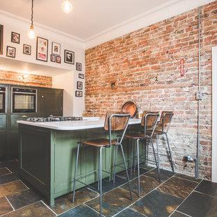サセックスの中サイズのインダストリアルスタイルのおしゃれなキッチン (シェーカースタイル扉のキャビネット、緑のキャビネット、珪岩カウンター、スレートの床、白いキッチンカウンター、茶色いキッチンパネル、レンガのキッチンパネル、パネルと同色の調理設備、茶色い床) の写真