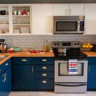 リッチモンドの小さいトランジショナルスタイルのおしゃれなキッチン (ドロップインシンク、フラットパネル扉のキャビネット、青いキャビネット、木材カウンター、白いキッチンパネル、サブウェイタイルのキッチンパネル、シルバーの調理設備の、クッションフロア、アイランドなし、ベージュの床) の写真