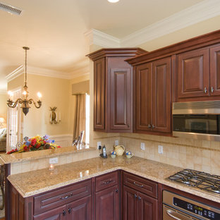 Mid-sized traditional u-shaped open plan kitchen in Atlanta with a double-bowl sink, raised-panel cabinets, dark wood cabinets, granite benchtops, beige splashback, ceramic splashback, stainless steel appliances, vinyl floors and a peninsula.