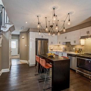 トロントの中サイズのコンテンポラリースタイルのおしゃれなキッチン (アンダーカウンターシンク、フラットパネル扉のキャビネット、白いキャビネット、木材カウンター、茶色いキッチンパネル、ボーダータイルのキッチンパネル、シルバーの調理設備、無垢フローリング、茶色い床) の写真