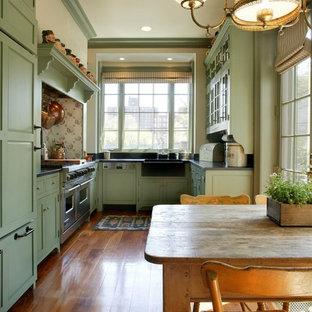 Mittelgroße Landhaus Küche in U-Form mit Landhausspüle, profilierten Schrankfronten, grünen Schränken, Speckstein-Arbeitsplatte, Küchenrückwand in Schwarz, Rückwand aus Stein, Elektrogeräten mit Frontblende und braunem Holzboden in New York