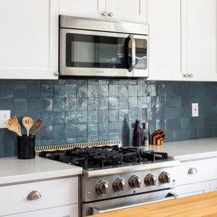 Exempel på ett mellanstort klassiskt vit vitt kök, med en nedsänkt diskho, skåp i shakerstil, vita skåp, bänkskiva i akrylsten, blått stänkskydd, stänkskydd i keramik, rostfria vitvaror, mörkt trägolv, en köksö och brunt golv