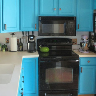 Design ideas for a mid-sized l-shaped eat-in kitchen in Denver with a double-bowl sink, raised-panel cabinets, turquoise cabinets, solid surface benchtops, white splashback, stainless steel appliances, medium hardwood floors, with island, red floor and white benchtop.