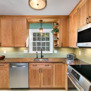 ワシントンD.C.の小さいトランジショナルスタイルのおしゃれなキッチン (アンダーカウンターシンク、シェーカースタイル扉のキャビネット、中間色木目調キャビネット、クオーツストーンカウンター、黄色いキッチンパネル、ガラス板のキッチンパネル、シルバーの調理設備、リノリウムの床、黄色い床) の写真