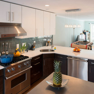 Example of a trendy l-shaped eat-in kitchen design in DC Metro with an undermount sink, flat-panel cabinets, brown cabinets, quartz countertops, gray backsplash, glass tile backsplash and stainless steel appliances