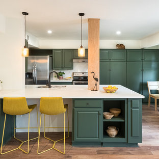 Inspiration for a mid-sized transitional eat-in kitchen in Austin with green cabinets, white splashback, limestone splashback, white benchtop, an undermount sink, raised-panel cabinets, stainless steel appliances, medium hardwood floors, a peninsula and brown floor.