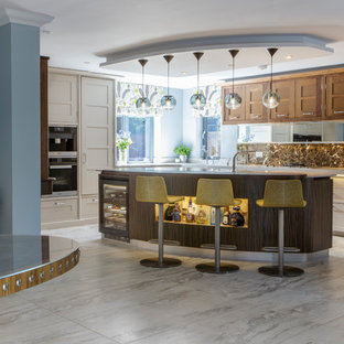 This is an example of a traditional l-shaped kitchen with recessed-panel cabinets, composite countertops, brown splashback, marble splashback, integrated appliances, ceramic flooring, an island, grey floors, medium wood cabinets and white worktops.