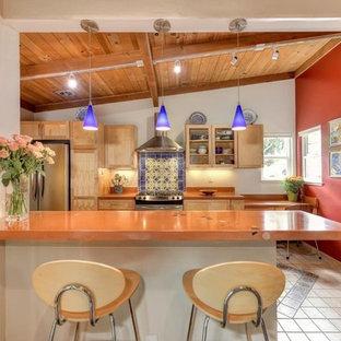 他の地域の中サイズの地中海スタイルのおしゃれなキッチン (シェーカースタイル扉のキャビネット、淡色木目調キャビネット、クオーツストーンカウンター、マルチカラーのキッチンパネル、セメントタイルのキッチンパネル、シルバーの調理設備の、磁器タイルの床、グレーの床、オレンジのキッチンカウンター) の写真