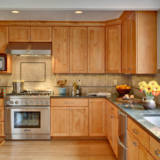 Example of a classic l-shaped eat-in kitchen design in Newark with granite countertops, an undermount sink, shaker cabinets, medium tone wood cabinets, multicolored backsplash, porcelain backsplash and stainless steel appliances
