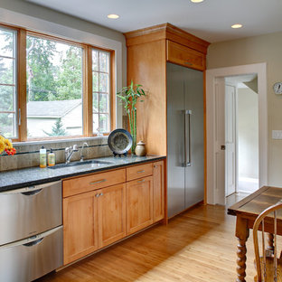 Inspiration for a timeless l-shaped eat-in kitchen remodel in Newark with stainless steel appliances, an undermount sink, shaker cabinets, medium tone wood cabinets, granite countertops, multicolored backsplash and porcelain backsplash