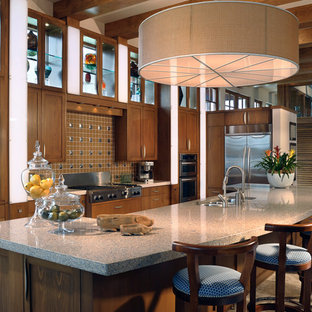 Bild på ett avskilt, stort tropiskt linjärt kök, med en undermonterad diskho, skåp i shakerstil, skåp i mörkt trä, bänkskiva i kvarts, brunt stänkskydd, stänkskydd i keramik, rostfria vitvaror, klinkergolv i porslin, en köksö och brunt golv