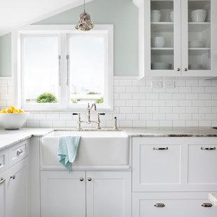 Modelo de cocina en U, clásica, de tamaño medio, con fregadero sobremueble, armarios con paneles empotrados, puertas de armario blancas, encimera de granito, salpicadero blanco, electrodomésticos de acero inoxidable, suelo de baldosas de porcelana y salpicadero de azulejos tipo metro