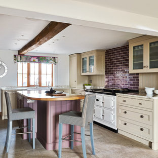 Inspiration for a farmhouse u-shaped enclosed kitchen in Cheshire with a belfast sink, shaker cabinets, beige cabinets, wood worktops, beige splashback, white appliances, an island, beige floors, brown worktops and exposed beams.