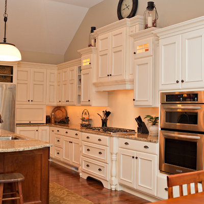 Inspiration for a timeless l-shaped eat-in kitchen remodel in Chicago with an undermount sink, white cabinets, granite countertops and stainless steel appliances