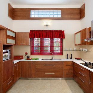 他の地域のアジアンスタイルのおしゃれなコの字型キッチン (ドロップインシンク、フラットパネル扉のキャビネット、中間色木目調キャビネット、ベージュキッチンパネル、アイランドなし、ベージュの床、白いキッチンカウンター) の写真