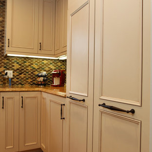 Photo of a mid-sized traditional u-shaped eat-in kitchen in Los Angeles with an undermount sink, recessed-panel cabinets, beige cabinets, granite benchtops, multi-coloured splashback, glass tile splashback, stainless steel appliances, bamboo floors, no island and beige floor.