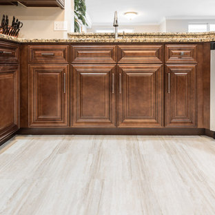 This is an example of a large traditional l-shaped open plan kitchen in Orlando with an undermount sink, raised-panel cabinets, medium wood cabinets, granite benchtops, stainless steel appliances, vinyl floors, with island, beige floor and beige benchtop.