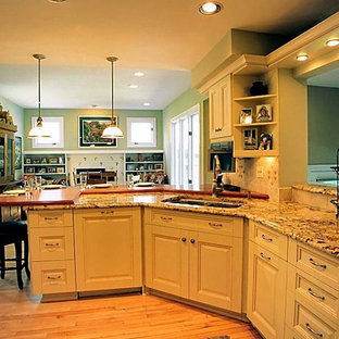 Inspiration for a mid-sized traditional u-shaped open plan kitchen in Chicago with a double-bowl sink, raised-panel cabinets, beige cabinets, granite benchtops, beige splashback, ceramic splashback, stainless steel appliances, medium hardwood floors and a peninsula.