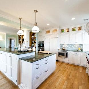 ニューヨークの広いビーチスタイルのおしゃれなキッチン (ドロップインシンク、フラットパネル扉のキャビネット、白いキャビネット、木材カウンター、青いキッチンパネル、石タイルのキッチンパネル、白い調理設備、無垢フローリング) の写真