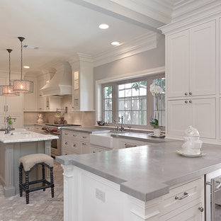 Photo of a mid-sized traditional u-shaped open plan kitchen in Houston with a farmhouse sink, recessed-panel cabinets, white cabinets, zinc benchtops, beige splashback, stainless steel appliances, brick floors and with island.
